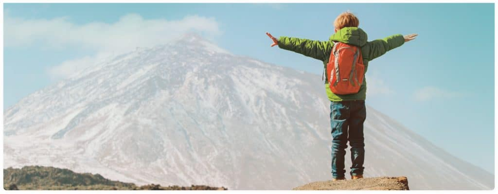 Young Boy Looking at Mountains with Arms Out